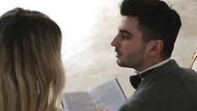 Een jong paar zit op een uitstekende bank kijkend door een boek stock videobeelden
