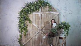 Een jong positief meisje zit op een uitstekende ladder en onderzoekt de camera royalty-vrije stock fotografie