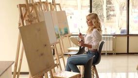 Een jong sexy meisje in een wit overhemd trekt op canvas in de studio voor tekening stock footage
