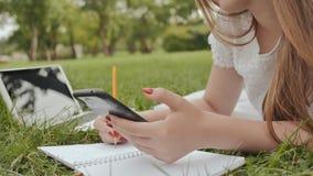 Een jong studentenmeisje die op het gras in het park liggen maakt nota's gebruikend een draagbare computer learning Voorbereiding stock video