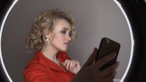 Een jong volwassen meisje in een rood jasje photographes zelf op de telefoon in een ring stock footage