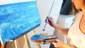 Een jong vrouwelijk kunstenaar het schilderen beeld op canvas met blauwe olieverven in haar workshop stock footage