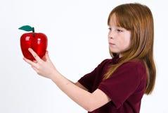 Vrouwelijk schoolkind die een duidelijke plastic appel houden royalty-vrije stock foto