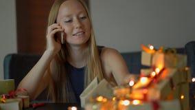Een jong vrouwenpak stelt en bespreking op een cellphone voor Heden in ambachtdocument wordt verpakt met een rood en gouden lint  stock video