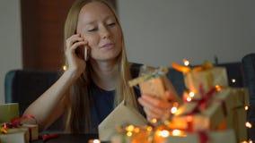 Een jong vrouwenpak stelt en bespreking op een cellphone voor Heden in ambachtdocument wordt verpakt met een rood en gouden lint  stock footage