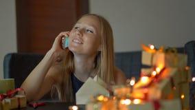 Een jong vrouwenpak stelt en bespreking op een cellphone voor Heden in ambachtdocument wordt verpakt met een rood en gouden lint  stock videobeelden