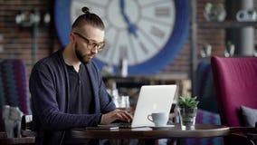 Een jonge aantrekkelijke hipster in een koffie, met een modern binnenland De man werkt aan zijn modieuze laptop Een ontwerper of  stock footage