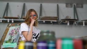 Een jonge aantrekkelijke kunstenaar met een borstel in haar handen en met een gezicht in de verf bevindt zich tegen de schilderse stock video