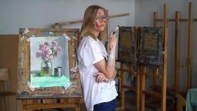Een jonge aantrekkelijke kunstenaar met een borstel in haar handen en met een gezicht in de verf bevindt zich tegen de schilderse stock footage