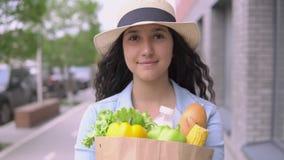 Een jonge aantrekkelijke vrouw in een een denimjasje en hoed draagt een kruidenierswinkelzak terwijl het hebben van een goede ste stock videobeelden