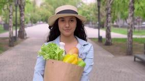 Een jonge aantrekkelijke vrouw in een een denimjasje en hoed draagt een kruidenierswinkelzak terwijl het hebben van een goede ste stock video
