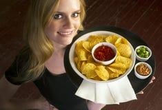De jonge Aantrekkelijke Vrouwelijke Server brengt het Voedsel van Salsa van de Spaanders van het Voorgerecht stock foto