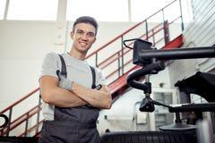 Een jonge aantrekkelijke werktuigkundige glimlacht terwijl het hebben van een rust stock afbeelding