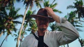 Een jonge actieve mens met een hoed met een snor onder de kokospalmen veegt zweet van zijn voorhoofd af en begroet dan stock videobeelden