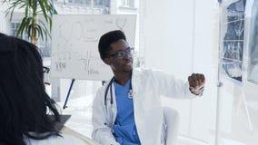 Een jonge afro Amerikaanse arts met röntgenstraal van vrouwelijk longen en bekken komt collega's samen en bespreekt geschiedenis  stock footage