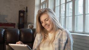 Een jonge Amerikaan die een tablet gebruiken maakt een orde in de de EU-opslag Een mooi blonde communiceert door een tablet A stock footage