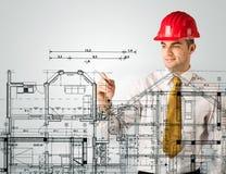 Een jonge architect die een huisplan trekken Stock Fotografie