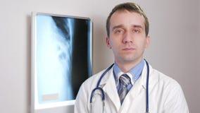 Een jonge arts bekijkt de camera en glimlacht Tegen de achtergrond het hangen röntgenstraal van de patiënt Overhemd met een band  stock videobeelden