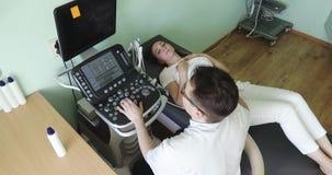 Een jonge arts die de vrouwen` s buikorganen onderzoeken die een ultrasone klankscanner met behulp van stock videobeelden