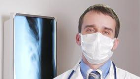Een jonge arts in een gezichtsmasker bekijkt de camera en glimlacht Tegen de achtergrond het hangen röntgenstraal van de patiënt  stock video