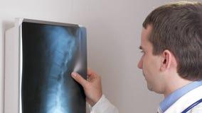 Een jonge arts onderzoekt de resultaten van een geduldige Röntgenstraal van ` s op de muur Analyseert van de thorax en de ribben stock videobeelden