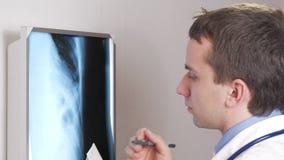 Een jonge arts schrijft de resultaten van een röntgenstraal van de patiënt met een pen op papier Röntgenstraal van de ribben Clos stock videobeelden