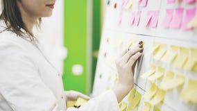 Een jonge artsenvrouw zet een sticker op een raad stock afbeeldingen