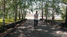 Een jonge atletische getatoeeerde mens die in het vierkant op de achtergrond van de stad dansen stock videobeelden