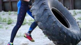 Een jonge atletische vrouw voert oefeningen uit gebruikend een groot zwaar tractorwiel, traint haar spieren Werpt het op stock footage