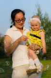 Een jonge een baby houden en moeder die borrelt blazen stock foto