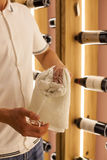 Een jonge barman veegt de glazen van de handdoekwijn bij het werk in het restaurant op de achtergrond van flessen wijn af Royalty-vrije Stock Foto's