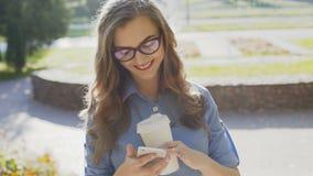 Een jonge bedrijfsdame in het park gebruikt een smartphone en het drinken latte stock videobeelden