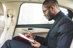Een jonge bedrijfsmens in een kostuum zit in de achterbank van een dure auto met een notitieboekje Bedrijfs onderhandelingen stock afbeelding