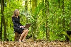 Een jonge bedrijfsvrouw die aan haar laptop in het bos werken Stock Foto