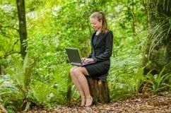 Een jonge bedrijfsvrouw die aan haar laptop in het bos werken Stock Afbeeldingen