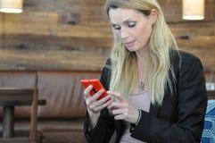 Een jonge bedrijfsvrouw die een slimme telefoon met behulp van Stock Afbeelding