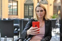 Een jonge bedrijfsvrouw die een slimme telefoon in openlucht met behulp van Stock Fotografie