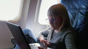 Een Jonge bedrijfsvrouw in glazenvliegen in een vliegtuig, gebruikt laptop Oud blonde Kaukasisch meisje 6 jaar stock video