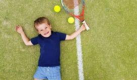 Een jonge blonde jongen die en op een tennisbaan, met racket en ballen glimlachen leggen Stock Afbeeldingen