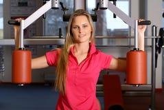 Een jonge blonde vrouw die in een geschiktheidsgymnastiek opleidt Stock Foto