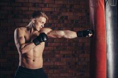 Een jonge bokser in zwarte handschoenen met een naakt torso werkt stakingen op ponsenzak uit Stock Fotografie