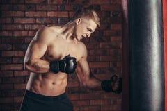 Een jonge bokser in zwarte handschoenen met een naakt torso werkt stakingen op ponsenzak uit Stock Afbeeldingen