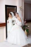 Een jonge bruid in een mooie kleding door een grote spiegel Stock Foto
