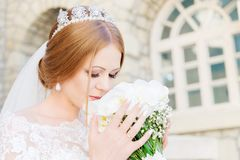 Een jonge bruid in een witte kleding snuift haar huwelijksboeket dat zorgvuldig door haar handen wordt gehouden stock foto