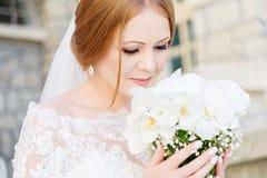Een jonge bruid in een witte kleding snuift haar huwelijksboeket dat zorgvuldig door haar handen wordt gehouden royalty-vrije stock afbeeldingen