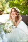 Een jonge bruid zit bij een glaslijst met haar die handen bij worden gevouwen royalty-vrije stock afbeeldingen