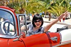 Een jonge Chinese verslaggever die uit haar golven dient een oude Amerikaanse auto in Royalty-vrije Stock Afbeeldingen