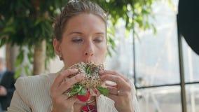 Een Jonge Dame Eating Sandwich in de Koffie royalty-vrije stock afbeelding