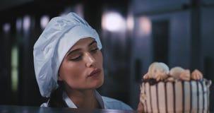 Een jonge dame met zwart haar die een chef-kokshoed dragen, geniet intens van de cake met haar vinger aangezien zij de smaak geni stock video