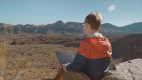 Een jonge die mens met laptop door bergachtig vulkanisch landschap wordt omringd stock video
